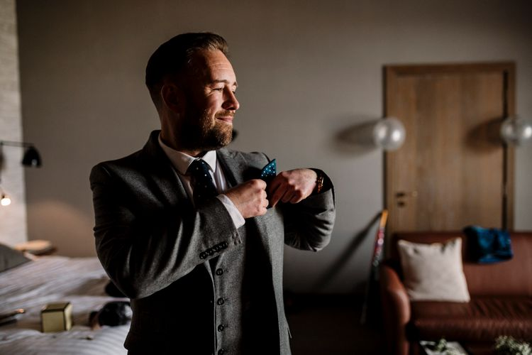 Groom in grey suit putting his green polka dot on