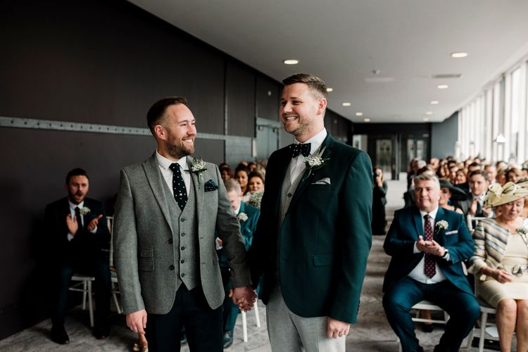 Grooms in grey and green suits exchange vows at Titanic Hotel Liverpool