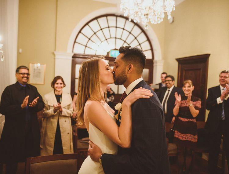 在伦敦Townhall婚礼上的新婚夫妇亲吻