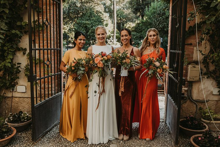 Bridesmaids in mustard, rust and orange dresses for earthy Andalusia wedding
