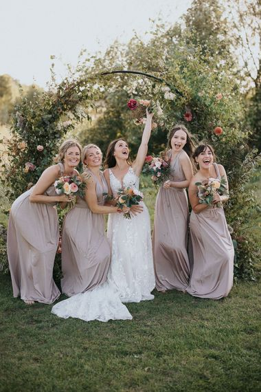 Bridesmaids in dusky pink dresses and bride in lace dress posing in front of the floral moon gate