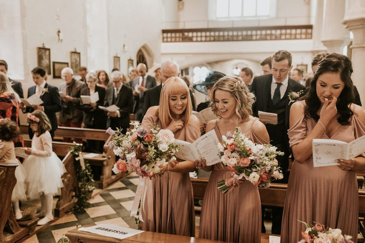 Bridesmaids in pink dresses inside the church