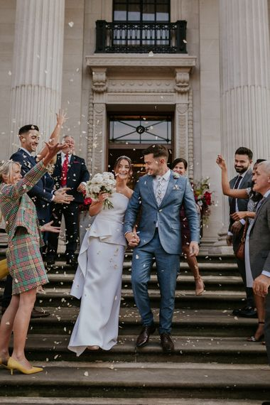 Confetti moment with bride in Roland Mouret strapless wedding dress