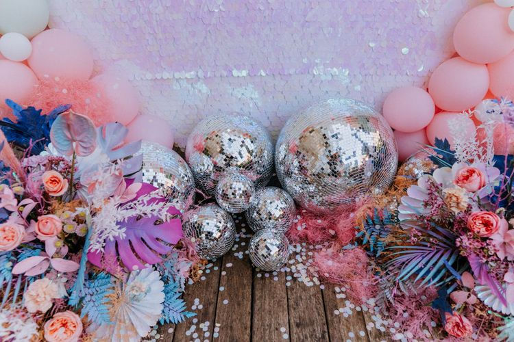 Holographic pastel wedding decor with sequin backdrop, disco balls and coloured monstera leaves