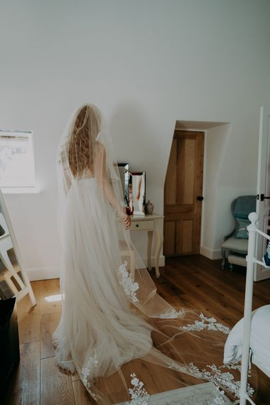 Bride in cathedral length veil with lace detail