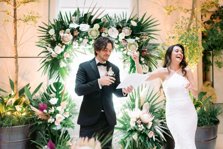 Newly-married couple enjoying speeches at their tropical themed wedding in London