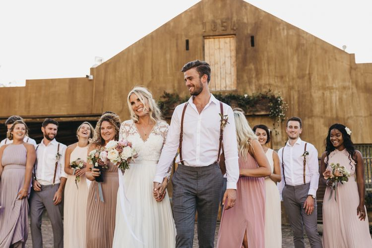 Bride and groom with bridesmaids in blush dresses