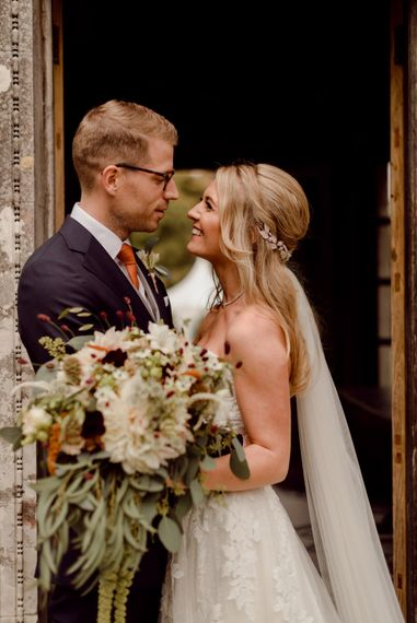 Bride and groom at Larmer Tree Gardens wedding with gorgeous bouquet