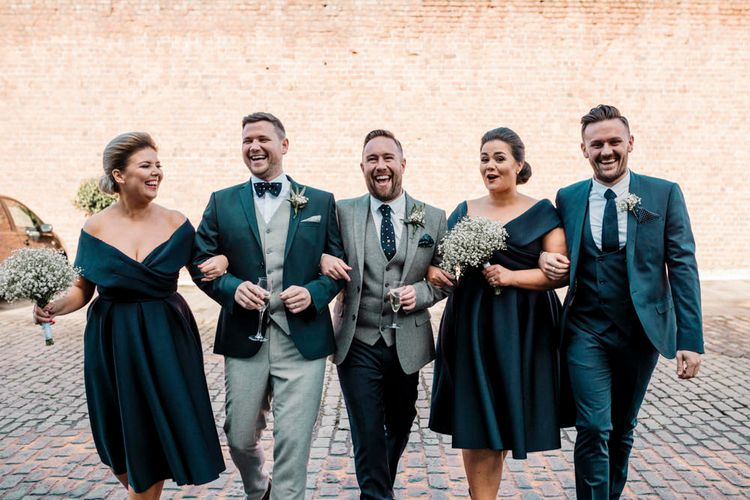 Wedding party portrait in teal green suits and dresses