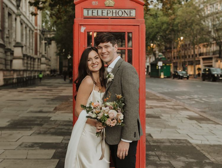 Bride and groom portrait next to a red telephone box in South Kensington