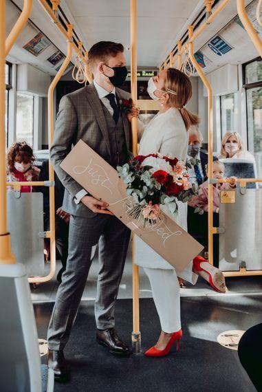 新娘和新郎穿着PPE在有轨电车上旅行