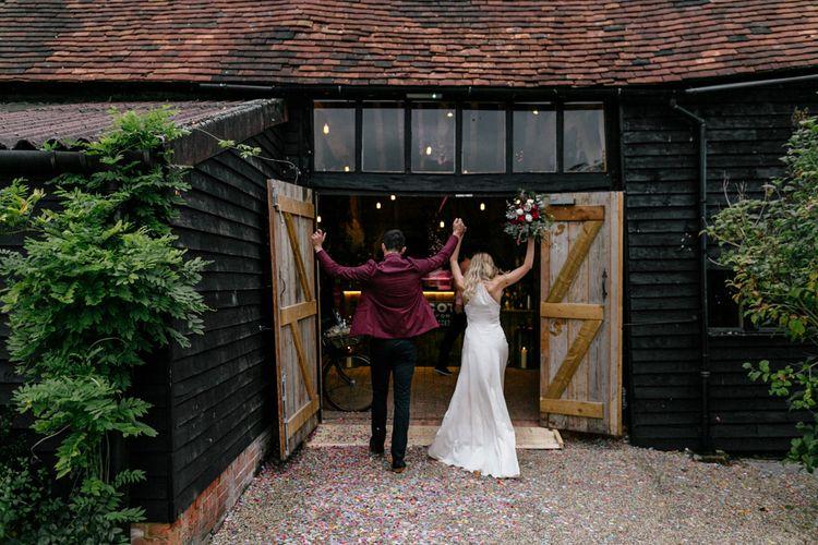 Bride and groom entering the barn reception at High Billinghurst Farm
