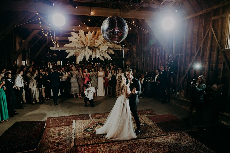 First dance in a barn decorated with rustic wedding decor
