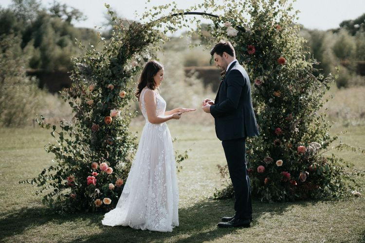 Bride and groom exchanging rings in front of a floral moon gate by Number Twenty Seven