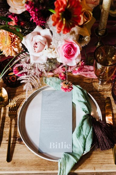 Place setting with coloured linen and menu card surrounded by bright flowers