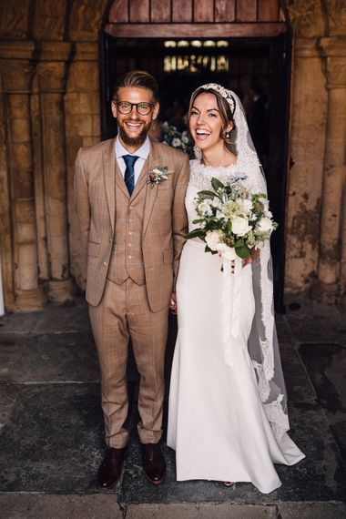Groom in brown check suit and bride in Sassi Holford wedding dress
