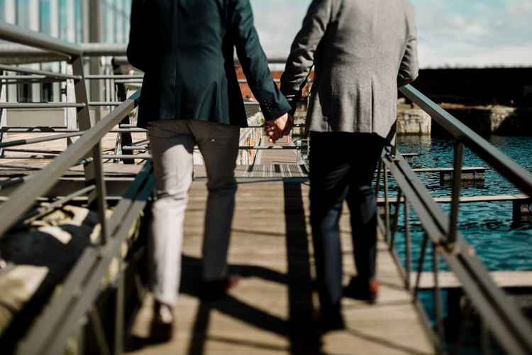 Grooms holding hands at Stanley Dock in Liverpool
