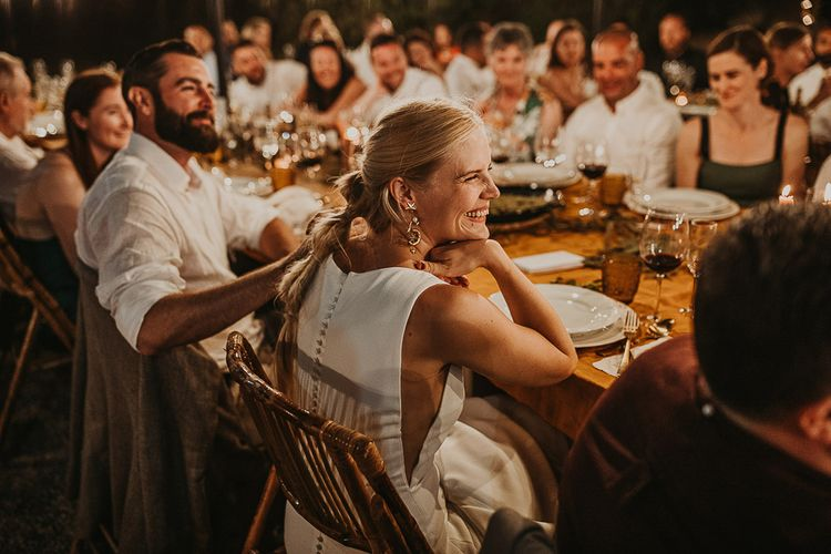 Bride with fishtail braid smiling during the festoon lit reception