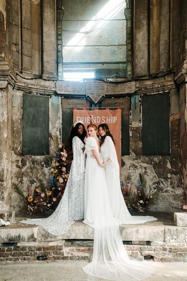 Brides in different casual wedding dresses embracing at the altar