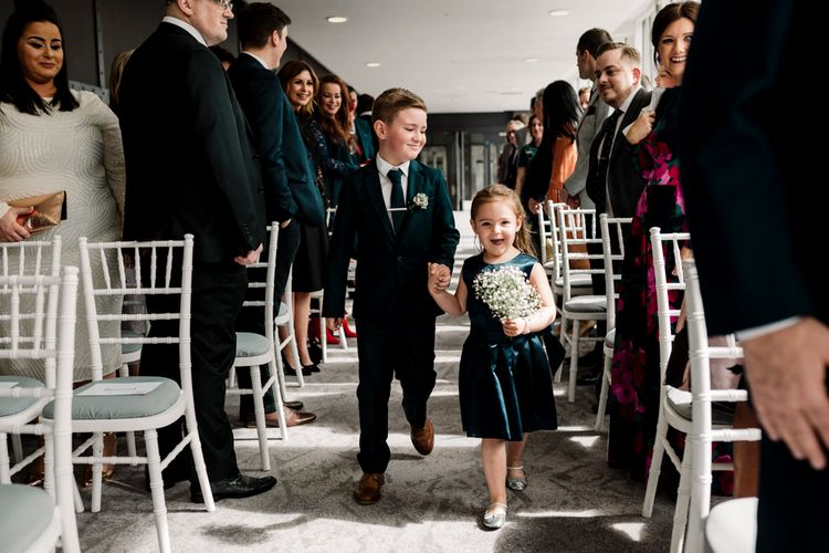 Page boy and flower girl walking down the aisle at Titanic Hotel Liverpool wedding