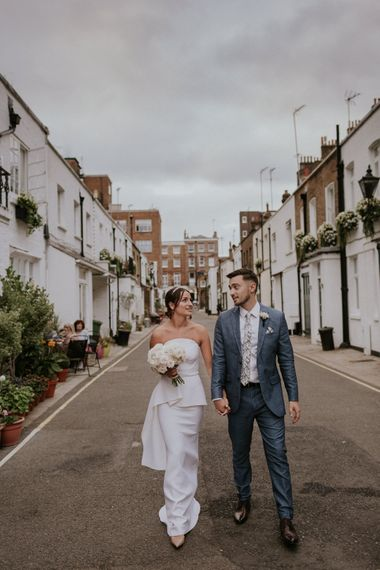 Bride in layered Roland Mouret dress with white bouquet holding hands with her husband
