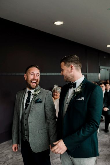Grooms in light grey and green suits laughing during the wedding ceremony at Titanic Hotel Liverpool