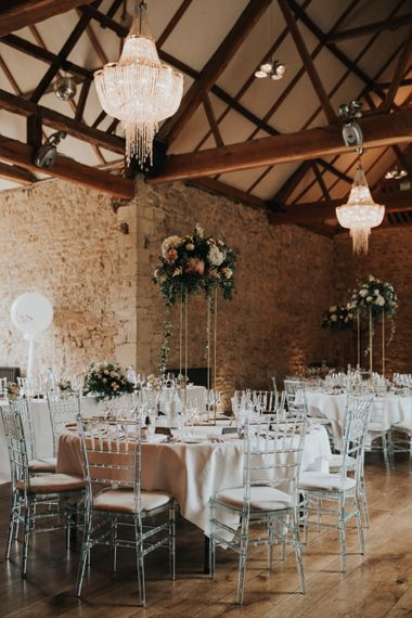 Notley Abbey wedding reception decor with tall floral centrepieces, chandeliers and ghost chairs