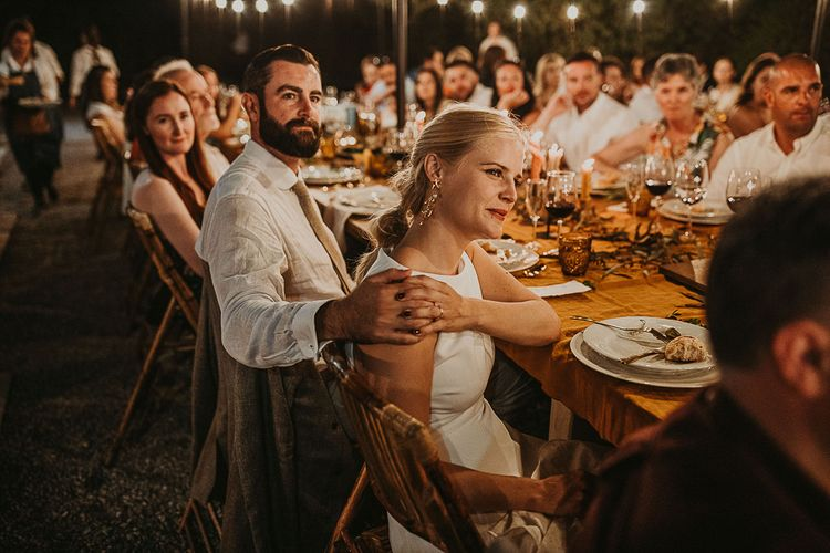 Bride and groom holding hands during outdoor wedding reception