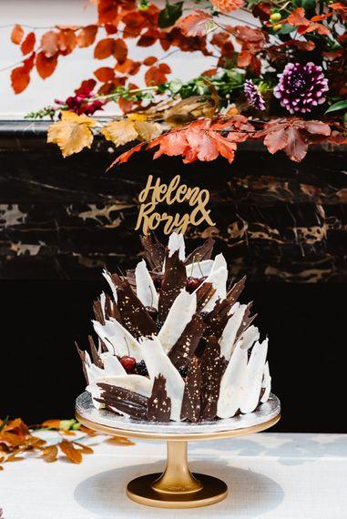 White and dark chocolate shard wedding cake design and gold cake topper