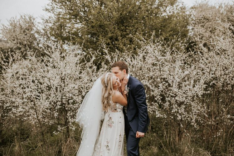 Bride and groom kissing by the Spring blossom