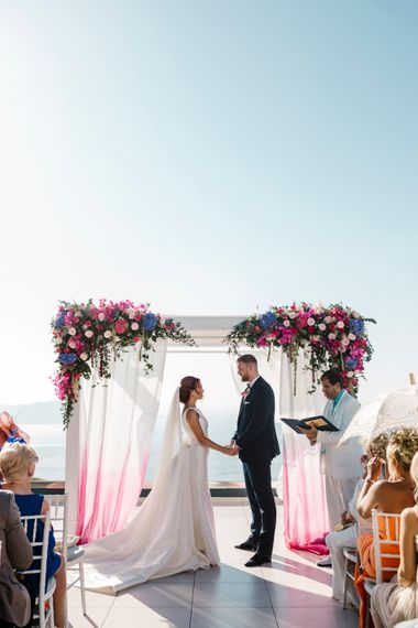 Bride and groom exchanging vows in front of a brightly coloured flower arch