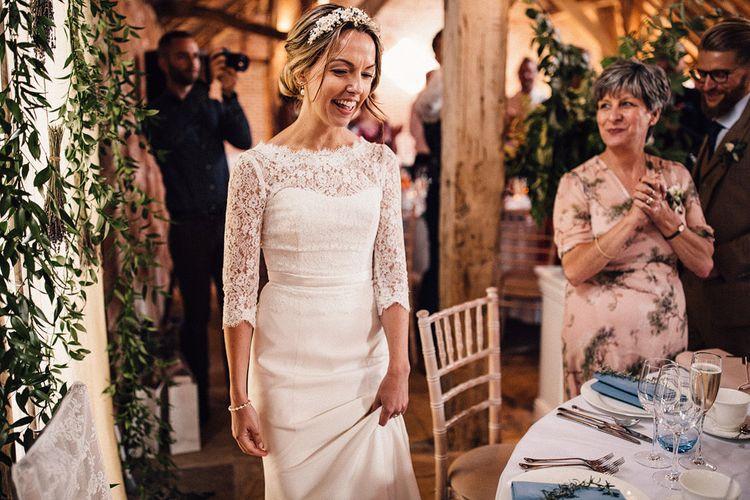 Bride in lace Sassi Holford wedding dress entering The Long Barn wedding reception