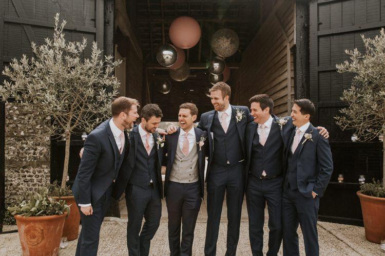 Groomsmen in Navy suits with pink ties