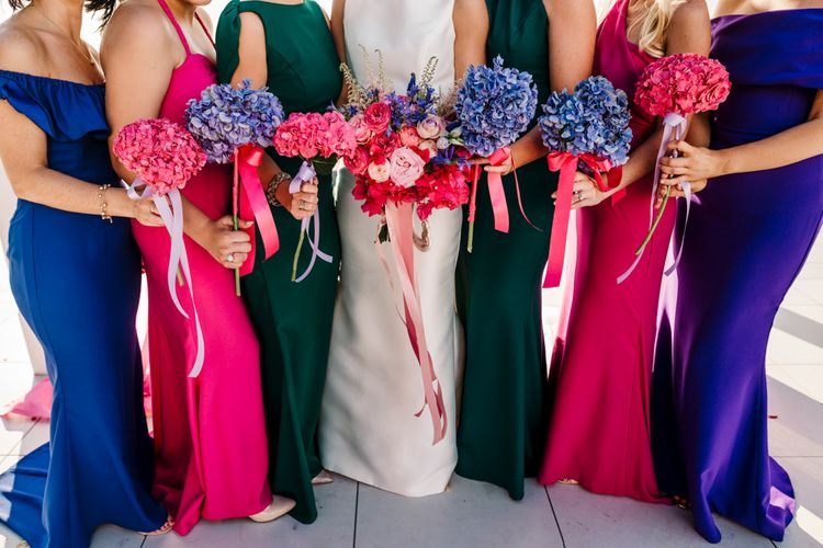 Bridesmaids in pink and green dresses holding blue hydrangea bouquets