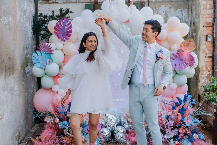 Bride and groom dancing in front of their sequin, glitter balls and balloon wedding altar