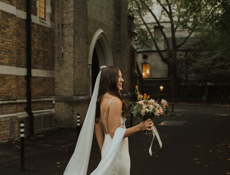 Stylish bride in slip wedding dress at church micro wedding
