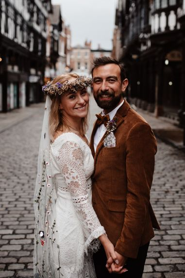 Boho bride in lace dress, embroidered veil and flower crown and groom in cord jacket