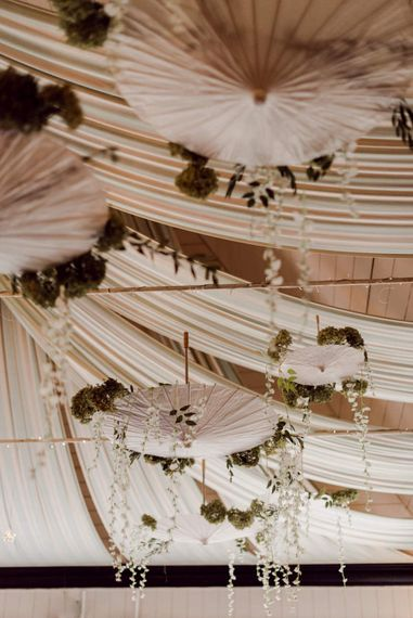 White umbrella decor from the bride and grooms travels