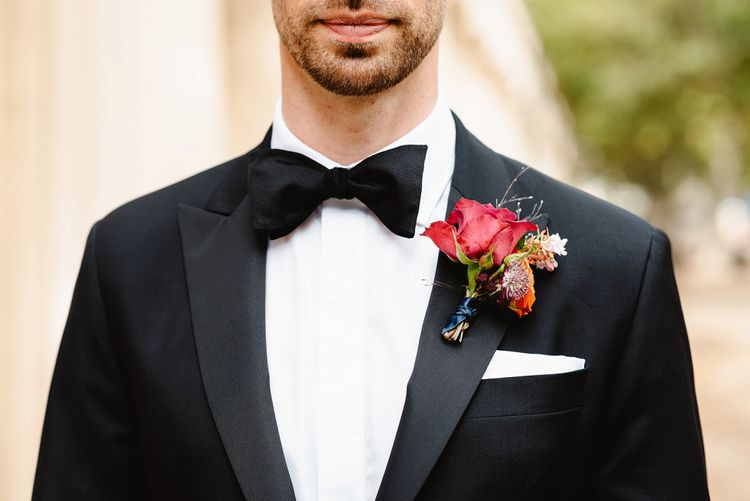 Red buttonhole at Autumn black tie wedding