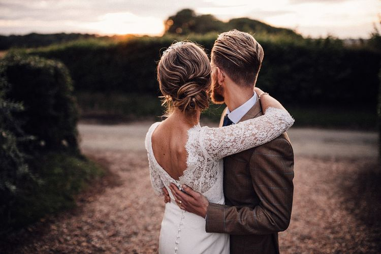 Bride in lace long sleeve wedding dress embracing her groom at dusk