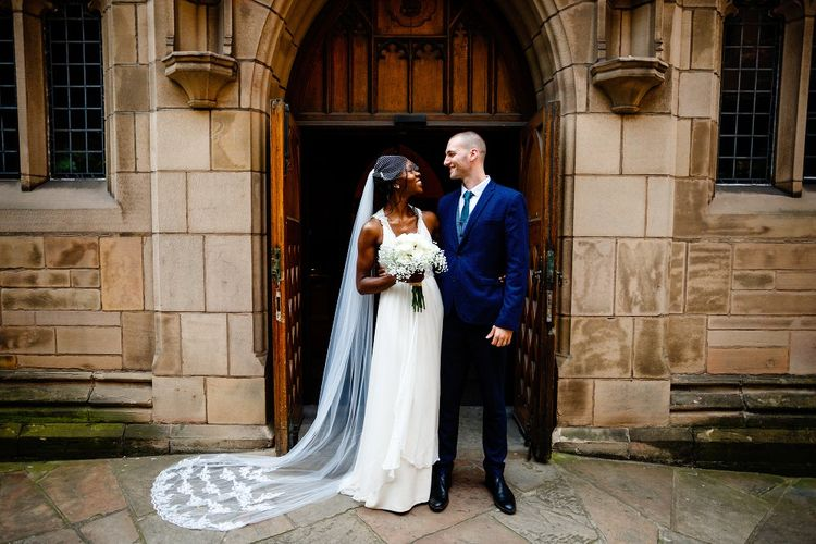 Bride in halterneck Jenny Packham wedding dress and lace edged cathedral length veil