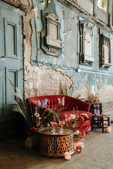 Intimate seating area with red velvet sofa, cocktails and cake table