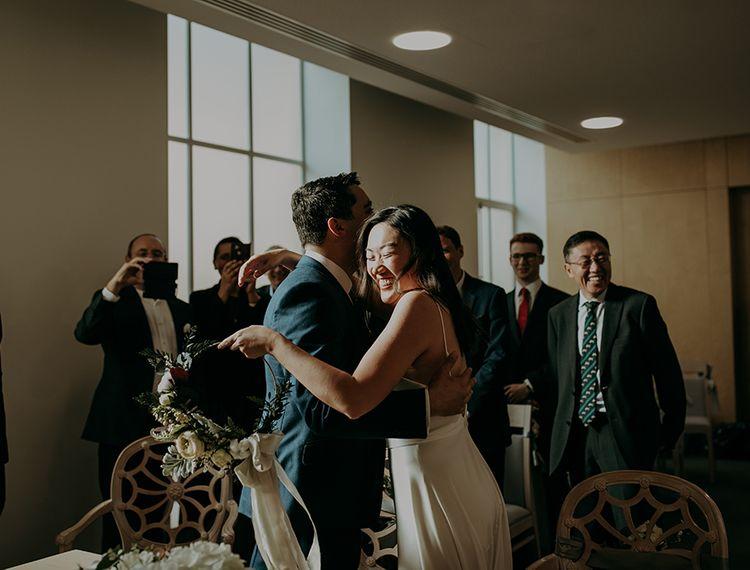 抱着雨伞拥抱她的新娘在圣坛上