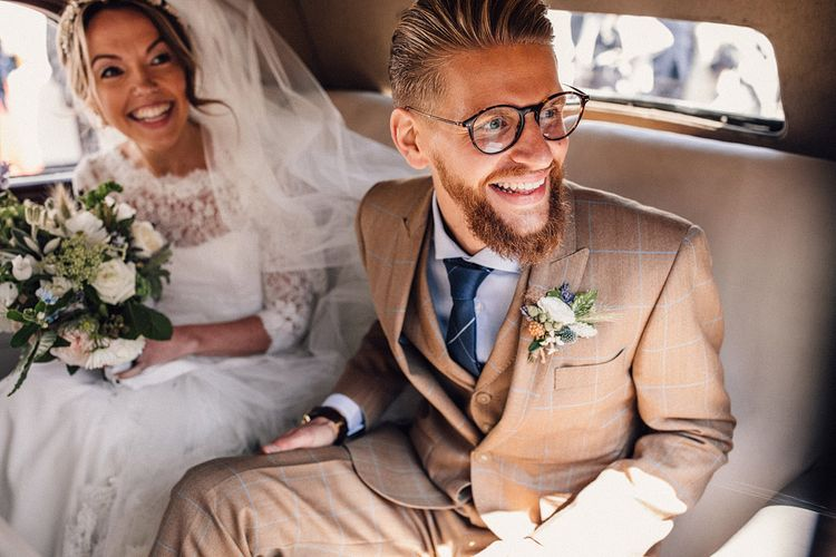 Groom in check suit and bride in lace edged veil