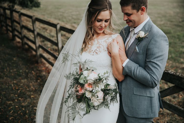 Bride in lace wedding dress and groom in grey suit for a classic wedding at Notley Abbey