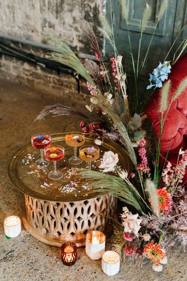 Gold platter of cocktails in coupe glasses filled with edible flowers