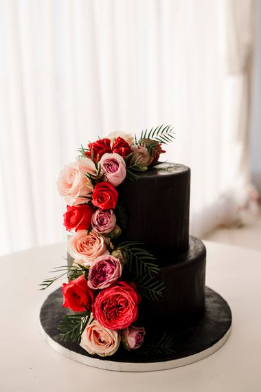 Black wedding cake with bright pink flowers for Santorini wedding