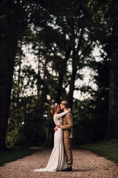 Bride and groom kissing in the forest at The Long Barn wedding