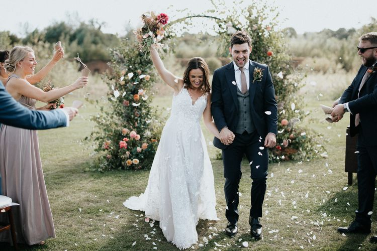 Bride and groom just married at outdoor wedding with floral moon gate