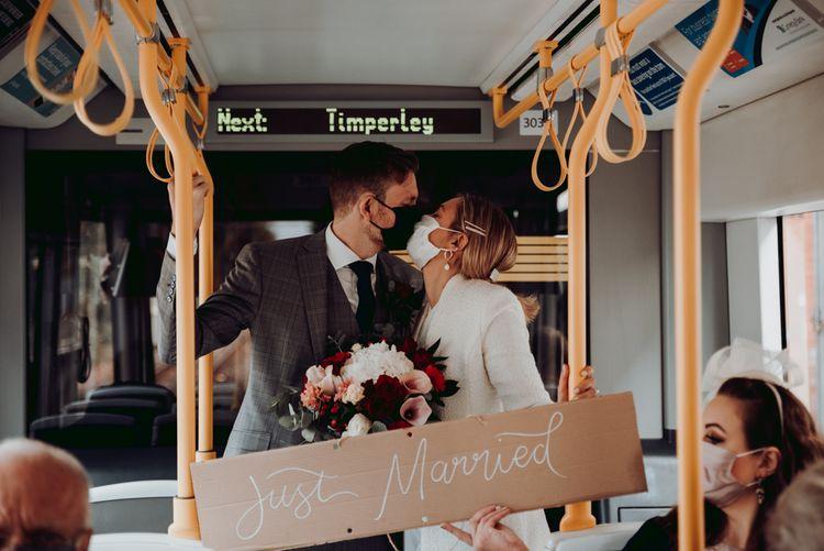 新郎新娘捧着纸板在电车上亲吻新婚夫妇婚礼标志
